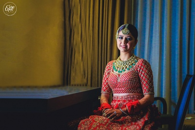 The bride wearing a traditional red embellished lehenga, paired with large pokli and emerald statement jewellery.