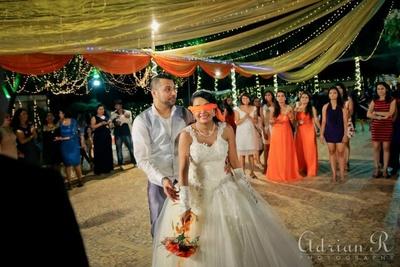 Netted gold drapes and light series. Orange festoons across the wedding venue