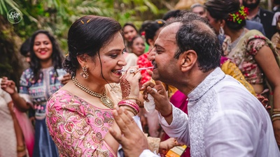 a candid capture of the parents playing fun games at the mehendi