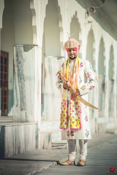 Unique groom attired in a white bandhgala sherwani with colorful silk embroidery, matching peach sehra and traditional sikh accessories