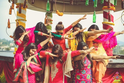 Candid wedding photography of the bride and her bridesmaids in a quirky pose