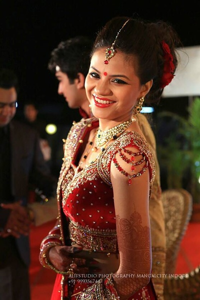 Red velvet choli embellished with stones, crystal adorned strings on the sleeves