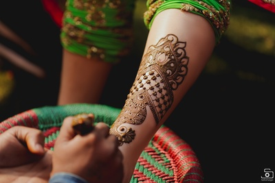 Beautiful mehendi designs being applied on the bride's arm!