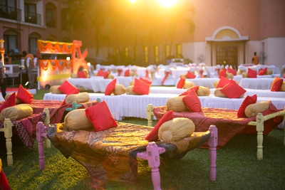 Ethnic benches and bolsters style seating for an outdoor sangeet event