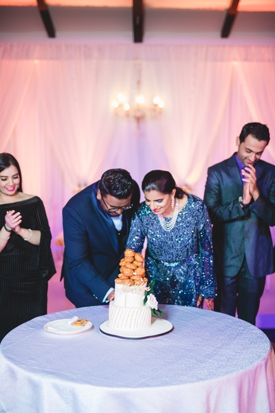 The bride and groom cutting an unconventional cake at their reception ceremony.