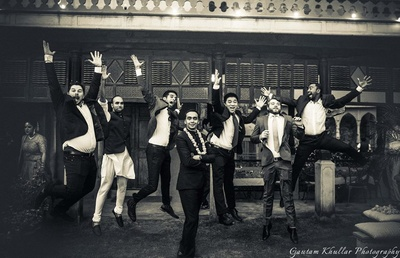 Groom and groomsmen posing for a quirky wedding pic .
