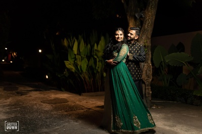The bride wearing  a green emerald gown and the groom in black sherwani