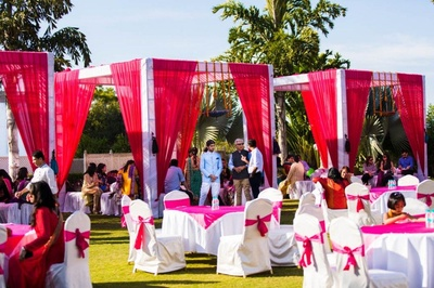 Outdoor pre wedding function arranged with fuchsia cabanas, tie backs and white table and chair covers