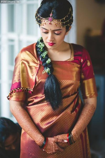 Wearing Kanchipuram maroon saree, coorgi style, with minimal gold jewellery and multi strand maang tikka !
