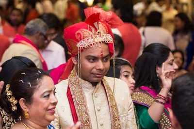 Groom wearing a beige textured silk sherwani beset with white ethnic embroidery paired with a red and gold safa offset with paisley patterns