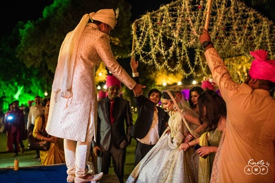 Bride helped onto the mandap by the groom during the wedding