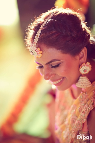 Traditional bride wearing floral jewellery for her mehndi function