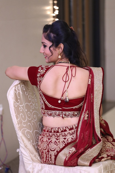 Maroon bridal lehenga styled with a matching cut-out tie back choli