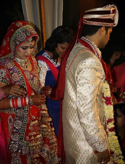 Groom wearing a tradtional cream sherwani to match the bride's attire