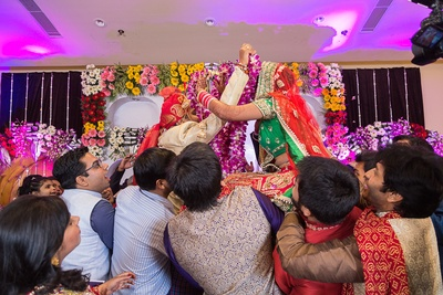 Wedding venue decked with clustered fresh flower arrangements and focus lights