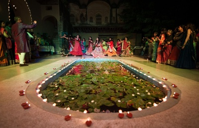 Performing for sangeet ceremony in an open space decorated simply with diyas and fairy lights