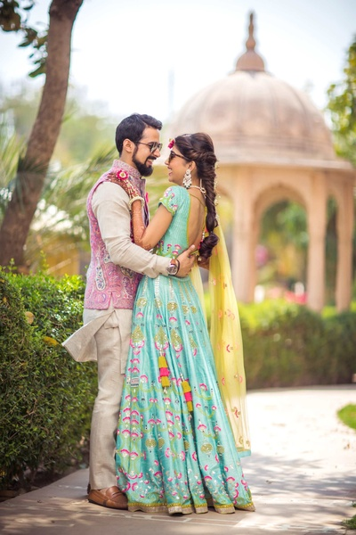 The bride and groom pose in their colorful outfits for mehndi function at Radisson Blu Udaipur
