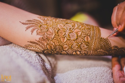 Intricately patterned mehndi design featuring roses and swirls as the bridal mehendi design