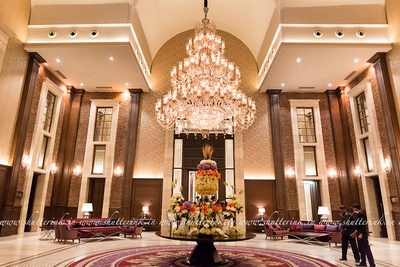 Opulent wedding venue with a royal crystal chandelier and floral centerpieces