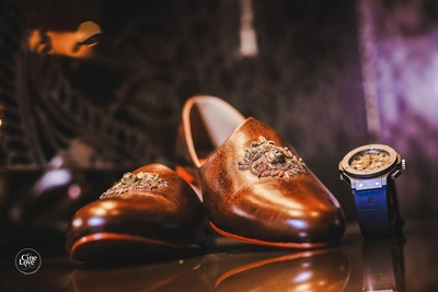 The grooms shining new brown juttis and stylish sports watch.