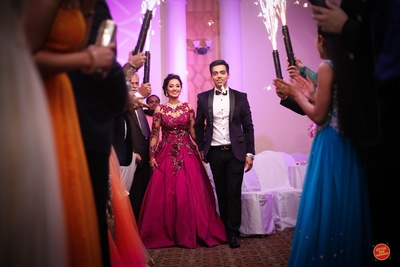 Bride wearing megenta pink gown styled with diamond neck piece and earrings and groom in black pants and coat with white shirt.