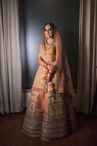 The bride looks beautiful in this wedding lehenga- a mix of beige, pink, gold, and apricot.