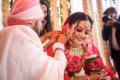 The groom tying the mangal sutra to the bride