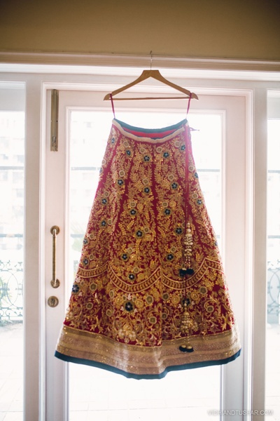 Red wedding lehenga decked with heavy embroidery, gold thread work, gold sequins work and crystal border