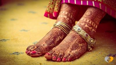 Indian bridal mehendi designs adorned with an ethnic floral patterned anklet