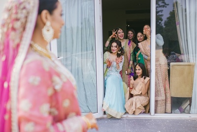 the bridesmaids in awe of the beautiful bride decked up for her wedding