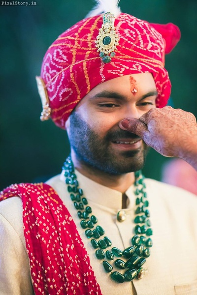 Gaurav dressed up in off white bandhgala paired with red bandhani printed turban styled with green stone neckpiece.