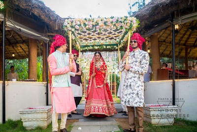 the bride walking under a phoolon ki chaadar with her brothers