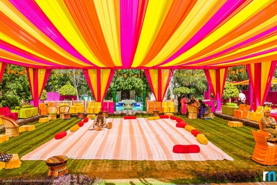 Pink, orange and yellow color coordinated decor with bolsters, matching chair covers- A perfect Mehendi setup