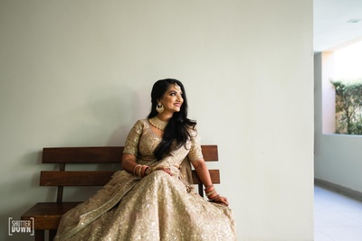 the bride looking beautiful in a bronze- golden lehenga by sabyasachi on her wedding day