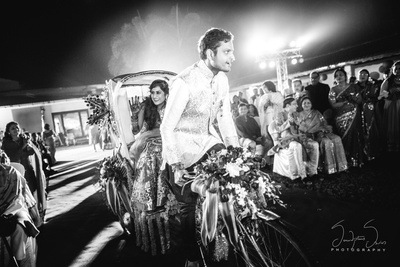 Bride and groom entering their sangeet ceremony on a Rickshaw.