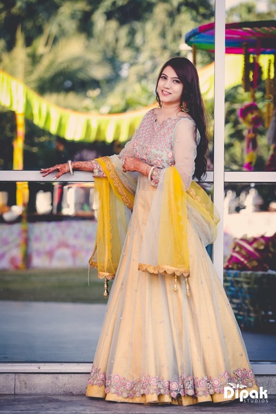 Manjot wearing a peach and yellow lehenga for the mehndi ceremony at JW Marriott, Chadigarh