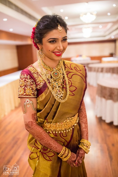 Apoorva dressed in a gold silk saree with maroon floral designs and zari embroidery.