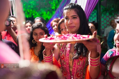 Sister of the bride welcoming the groom with pooja thaali full of rose petals