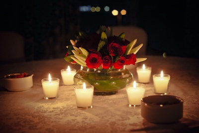 Rose and seasonal wihite flowers immersed in water vase and surrounded by tea lights as table centerpieces