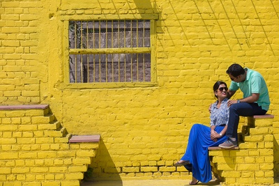Pre-wedding photographs taken in front of a rustic yellow brick wall