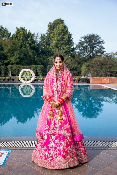 the beautiful bride dressed in a fuschia pink lehenga for her wedding