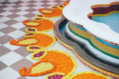 Rangoli done with Marigold flowers in paisley and diya shape with Rose petals
