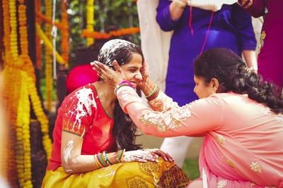 Bride Vasundhra wore this beautiful red and yellow cotton lehenga with minimal styling for the Haldi Ceremony.