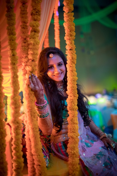 Bride sitting on floral swing showing off her mehndi design
