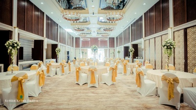 Banquet hall in Four Seasons, Worli decorated in hues of white and gold tie backs, floral topiary standies as centerpieces
