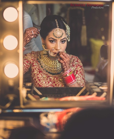 Bride adorned in beautiful kundan and diamond bridal neck piece, nath, maang tikka and passa for the wedding day.