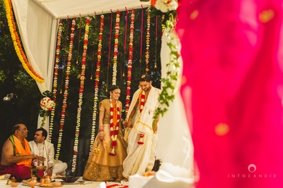 Simple wedding mandap decorated with white drapes, Marigold strings and floral strings