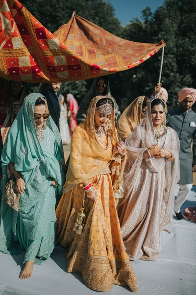 The bride walking towards the mandap under a chaadar.