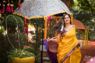 The bride looks like elegant in an ochre and purple kanjeevaram saree.
