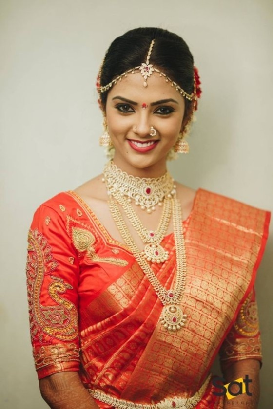 036716edb1 This South Indian bride looks pretty in this coral coloured saree with  maggam work in peacock motifs. The design along the neckline of the blouse  adds a ...